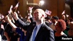 Di dân vẫy cờ sau khi đọc lời tuyên thệ trong lễ nhập quốc tịch để trở thành công dân Mỹ tại Cơ quan Lưu trữ Quốc gia Hoa Kỳ, 18/6/2014.