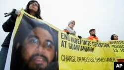FILE - Human rights activists hold a banner with a picture of Saudi national Guantanamo detainee Shaker Aamer during a rally near the White House in Washington, Jan. 11, 2013.