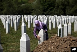 FILE - A woman touches the tombstone of a relative at the Potocari, memorial complex near Srebrenica, 150 kilometers northeast of Sarajevo, Bosnia, July 10, 2015.