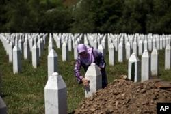 FILE - A woman touches the tombstone of a relative at the Potocari, memorial complex near Srebrenica, 150 kilometers northeast of Sarajevo, Bosnia, July 10, 2015.