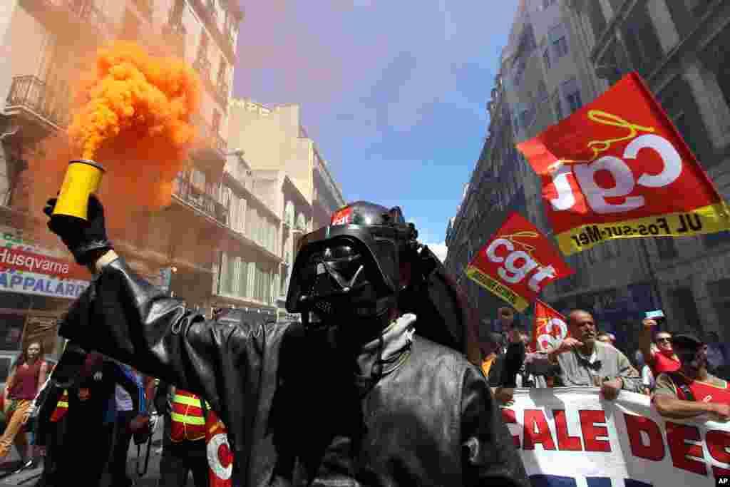 កម្មករម្នាក់ពីរោងចក្រដែក ArcelorMittal ក្នុងក្រុង Fos-sur-Mer ដោយពាក់ស្រោមមុខតួតុក្កតា Darth Vader ដុតភ្លើងពណ៌នៅអំឡុងពេលបាតុកម្មមួយនៅក្រុង Marseille ភាគខាងត្បូងប្រទេសបារាំង។