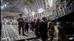 Penumpang Afghanistan menaiki C-17 Globemaster III Angkatan Udara AS selama evakuasi Afghanistan di Bandara Internasional Hamid Karzai di Kabul, Afghanistan. (Foto: Angkatan Udara AS via AP)