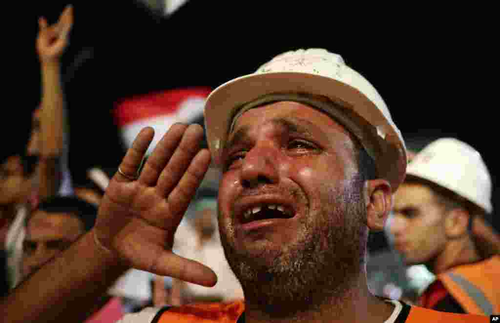 A supporter of Egypt's ousted President Mohamed Morsi cries while saluting the Egyptian flag at Rabaa al-Adawiya mosque, Nasr City, Cairo, Egypt.
