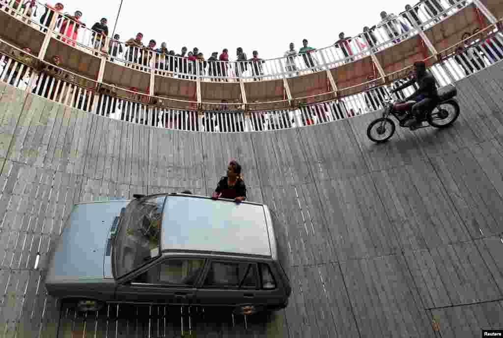 អ្នកសម្តែងឈុតគ្រោះថ្នាក់ម្នាក់ជិះម៉ូតូនិងឡានលើជញ្ជាំងនៃ «Well of Death» នៅក្នុងពិពណ៌ Magh Mela ក្នុងទីក្រុង Allahabad ប្រទេសឥណ្ឌា។