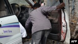 A resident tries to remove the remains of the driver of the female MP and former singer Saado Ali Warsame after gunmen opened fire at her car on July 23, 2014 killing her and her driver in Mogadishu.