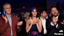 تصویر وسط - کیتی پیری، آواز خوان مشهور امریکا درحال تشویق کاندید دموکرات ها در گردهمایی آیوا در جایگاه حاضر می شود.