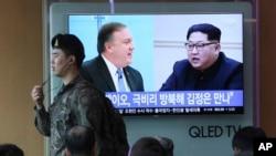 一名韩国军人从首尔火车站播报显示蓬佩奥和金正恩图像的新闻节目的电视屏幕前走过。(2018年4月18日)