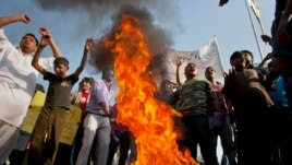 Pakistani Christians chant slogans after they burn a tire during a demonstration demanding that the government rebuild their homes after they were burned down following an alleged blasphemy incident, in Islamabad, Pakistan, March 10, 2013.