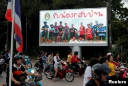 "FILE - A board showing ""Welcome home, boys"" is seen after rescue efforts began for the 12 schoolboys and their soccer coach trapped in Tham Luang cave, in Chiang Rai, Thailand, July 9, 2018."