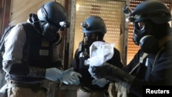 2013年8月29日聯合國調查人員在敘利亞首都大馬士革手持搜集到的化學武器樣本的照片
