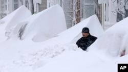 """John Silver berusaha membersihkan tumpukan salju yang """"mengubur"""" mobilnya di depan rumahnya di kota Boston, hari Sabtu (9/2)."""