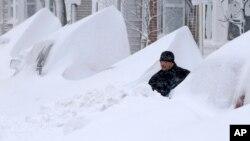 Un hombre trata de abrirse paso en busca de su auto entre la nieve a la puerta de su casa en Boston, luego de la severa nevada que entre viernes y sábado azotó el noreste de EE.UU.