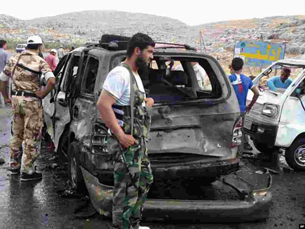 This citizen journalism image provided by Edlib News Network shows Syrian rebels with damaged cars after a car bomb exploded at a crossing point near Syria's border with Turkey, Sept. 17, 2013.