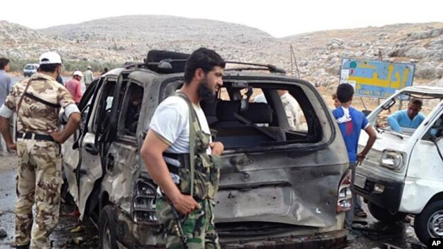 Syrian rebels look over damaged cars after a car bomb exploded at a crossing point near Syria's border with Turkey, Sept. 17, 2013.
