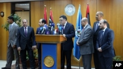 FILE - Fayez al-Saraj, flanked by members of the Presidential Council, speaks during a news conference at the Mitiga Naval Base in Tripoli, Libya, March, 30, 2016.