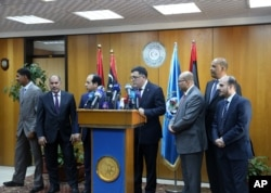 FILE - Fayez Seraj, flanked by members of the Presidential Council, speaks during a news conference at the Mitiga Naval Base in Tripoli, Libya, March, 30, 2015.