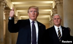 FILE - U.S. President Donald Trump gives a thumbs-up as he and Vice President Mike Pence depart the U.S. Capitol after a meeting to discuss tax legislation with House Republicans, Nov. 16, 2017.