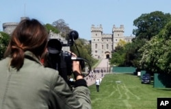 FILE - A camera woman films the Long Walk toward Windsor Castle in Windsor, England, May 15, 2018.