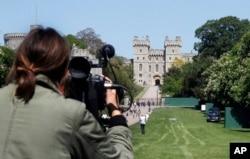 FILE - A camera woman films the Long Walk toward Windsor Castle in Windsor, England, May 15, 2018.
