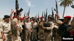Les membres des forces de sécurité irakiennes scandent des slogans à Bagdad le 13 Juin 2014., après que le président américain Barack Obama eut annoncé la possiblité de frappes militaires contre les insurgés
