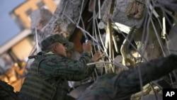 Soldados usan sus teléfonos celulares como linternas en la búsqueda de supervivientes del terremoto en Ecuador.