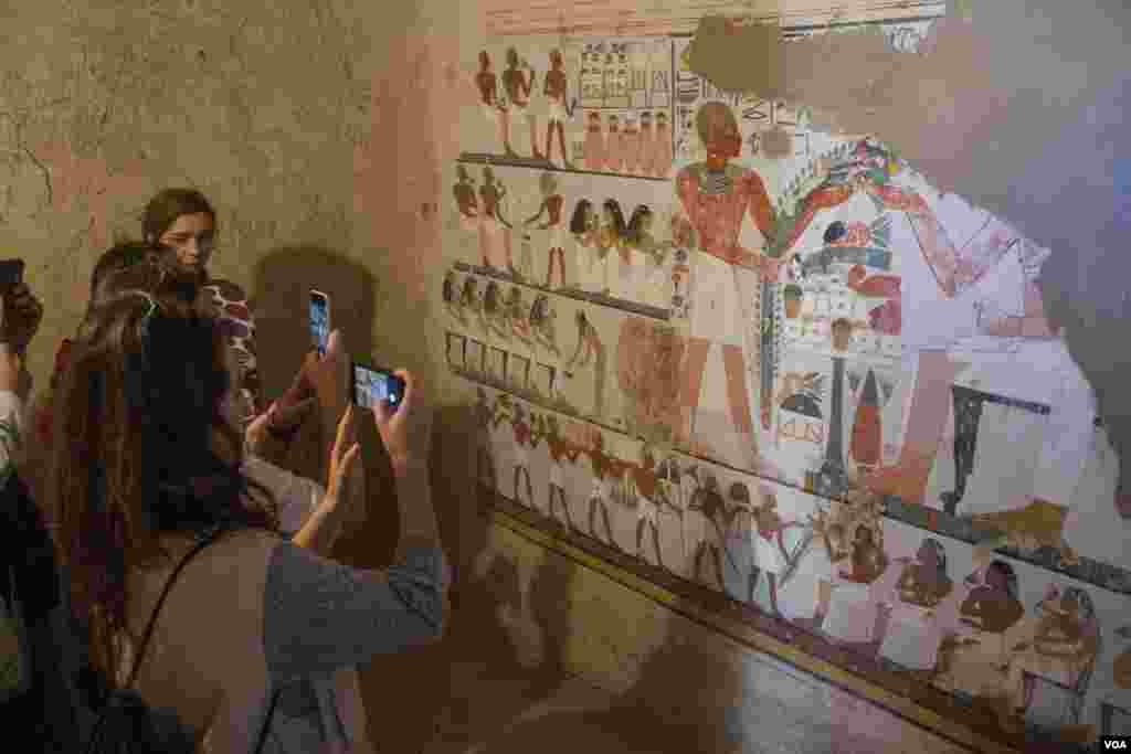 Tourists snap photos of a mural depicting a funeral inside the recently discovered Kampp 161 tomb in the Draa Abul Naga necropolis on Luxor's west bank, Egypt, Dec. 9, 2017. (H. Elrasam/VOA)