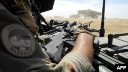 FILE - A soldier of France's Barkhane mission holds a weapon as he patrols in central Mali, in the border zone with Burkina Faso and Niger, Nov. 01, 2017.