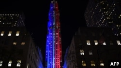 FILE - Rockefeller Center and Rockefeller Plaza is lit up in red and blue to mark the electoral progress of Hillary Clinton and Donald Trump and a map of the United States was superimposed on the skating rink, Nov. 7, 2016.