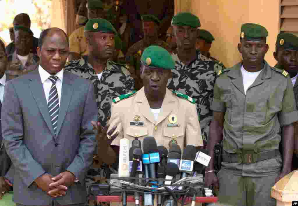Coup leader Capt. Amadou Haya Sanogo, center, with Burkina Faso Foreign Affairs Minister Djibril Bassole (left) addresses the press at junta headquarters in Kati, outside Bamako, Mali, April 1, 2012. The leader of Mali's recent coup says he is reinstating