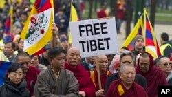 Ketua Abbot dari kekaisaran Kirti Monastery, Kyabje Kirti Rinpoche, empat dari kanan, memimpin pawai warga Tibet dan para pendukungnya dalam aksi unjuk rasa di Brussels (10/3).