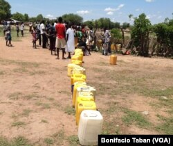 FILE - A long line of jerry cans waiting to be filled at the only borehole in a sector of Rhino refugee camp in Uganda that houses thousands of refugees.