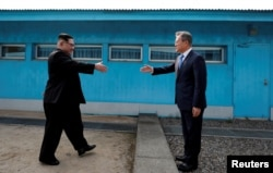 South Korean President Moon Jae-in and North Korean leader Kim Jong Un shake hands at the truce village of Panmunjom inside the demilitarized zone separating the two Koreas.