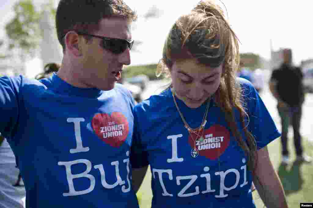 Supporters of the Israel's center-left Zionist Union party wear T-shirts bearing the names of the party's co-leaders, Isaac Herzog, also known by his nickname, Buji, and Tzipi Livni, during a campaign stop in the southern city of Ashdod.