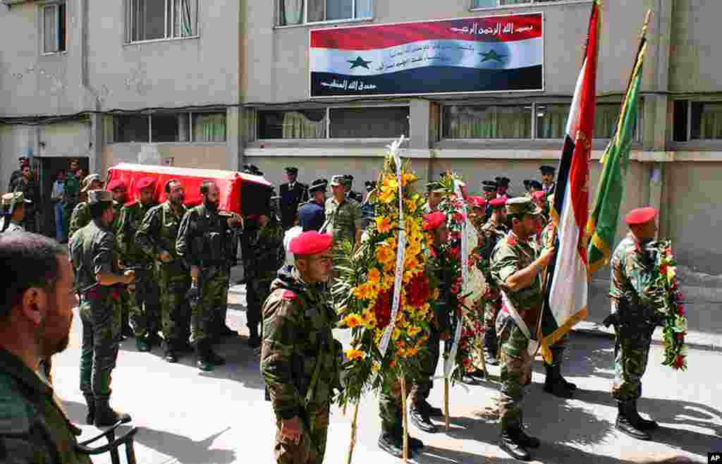 Syrian soldiers carry the coffin of the commander of the pro-government National Defense Forces, Hilal Assad, during his funeral at a hospital in Latakia province, March 24, 2014. (SANA)