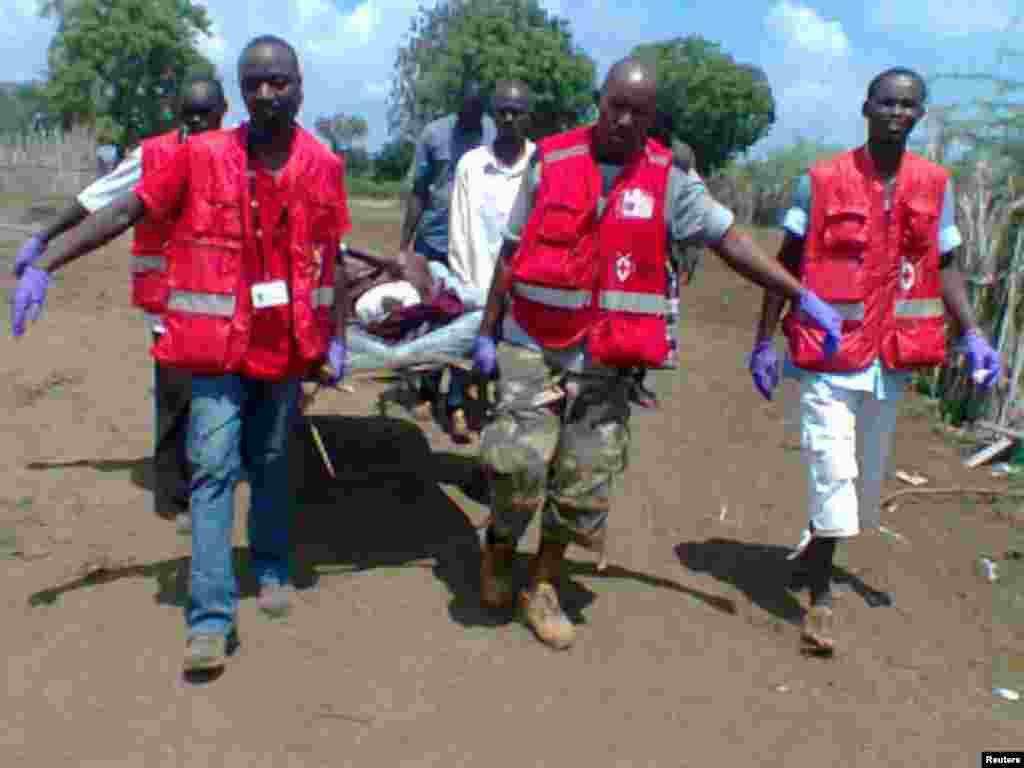 Members of the Kenya Red Cross carry an injured man after an attack in his village at Tana River district.