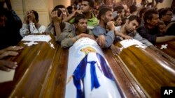 FILE - Relatives of Coptic Christians who were killed during a bus attack, surround their coffins, during their funeral service, at Abu Garnous Cathedral in Minya, Egypt, May 17, 2017. The Libya connection in the Manchester concert bombing and Friday's attack on Christians in Egypt has shone a light on the threat posed by militant Islamic groups that have taken advantage of lawlessness in the troubled North African nation to put down roots, recruit fighters and export jihadists to cause death and carnage elsewhere.