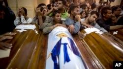 FILE FOTO - Kerabat umat Kristen Koptik yang terbunuh saat serangan bus, mengelilingi peti mati, saat pemakaman mereka di Katedral Abu Garnous di Minya, Mesir, 17 Mei 2017.