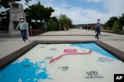FILE - Visitors walk by a map of two Koreas showing North Korea's capital Pyongyang and South Korea's capital Seoul at the Imjingak Pavilion in Paju, South Korea, near the border with North Korea, Sept. 24, 2021.