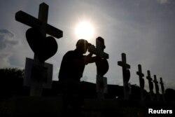 Un hombre escribe un mensaje en una de las cruces colocada en honor de las víctimas del tiroteo en la escuela secundaria Santa Fe, en Santa Fe, Texas. Mayo 21, 2018.
