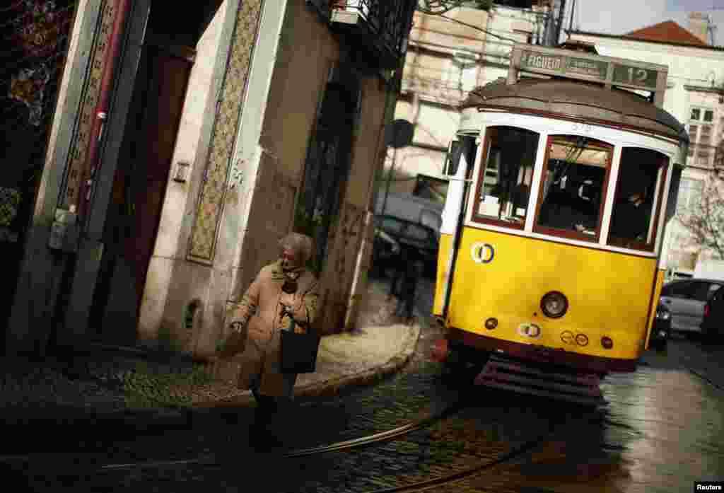 Một phụ nữ đi bộ gần một chiếc xe điện trong khu phố cổ Alfama, trong thủ đô Lisbon của Bồ Đào Nha. (Reuters)
