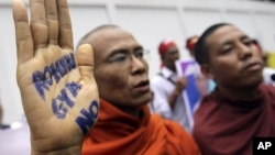 A Buddhist monk shows a message written in his palm to protest against the ethnic minority Rohingyas in Burma during a visit of Burma's President Thein Sein in Bangkok, Thailand, July 24, 2012.