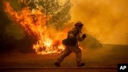 Vatrogasac trči dok pokušava da spasi kuću, dok požar besni kroz Lejkport, Kalifornija, 31. jula 2018.