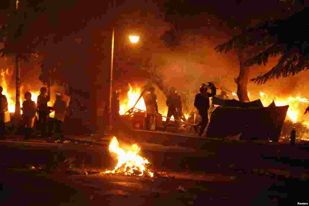 Police burn tents of protesters who staged a sit-in for weeks in front of the presidential palace, during clashes between protesters and police, in Cairo, Feb. 1, 2013.