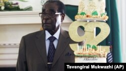 FILE: Zimbabwean President Robert Mugabe stands next to his Birthday cake at State House in Harare, Monday, Feb. 22, 2016.