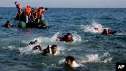 Des migrants finissent leur parcours à la nage après que leur bateau se soit renversé près de l'île de Lesbos, Grèce, le 20 septembre 2015.