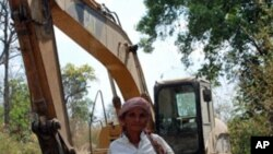 Puth La, 62, an ethnic minority Suy woman, standing next to a digger that villagers say is being used by a Singaporean company to destroy thousands of hectares of land they claim as their own in the province of Kampong Speu, south-west of the capital Phno