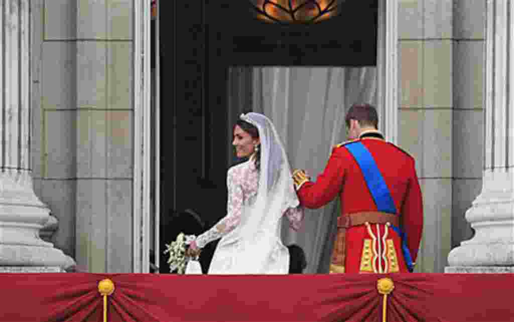 Britain's Prince William and his wife Kate, Duchess of Cambridge go back inside from the balcony of Buckingham Palace after the Royal Wedding in London Friday, April, 29, 2011. (AP Photo/Matt Dunham)