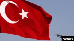 A Turkish Air Force F16 jet fighter takes off from an air base as Turkey's national flag