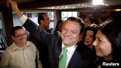 Costa Rica's ruling party candidate Johnny Araya (C) greets supporters next to his wife Sandra Leon (R) as he arrives for a news conference where he announced he was quitting the presidential race, in San Jose, Costa Rica, March 5, 2014.