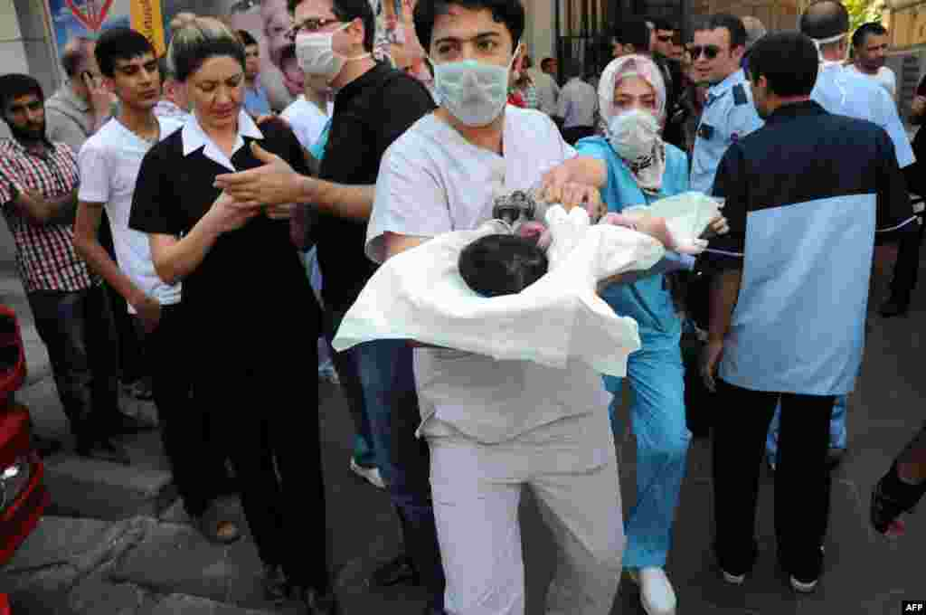 Doctors evacuate a baby from a hospital when a fire breaks out in the center of Diyarbakir, Turkey.